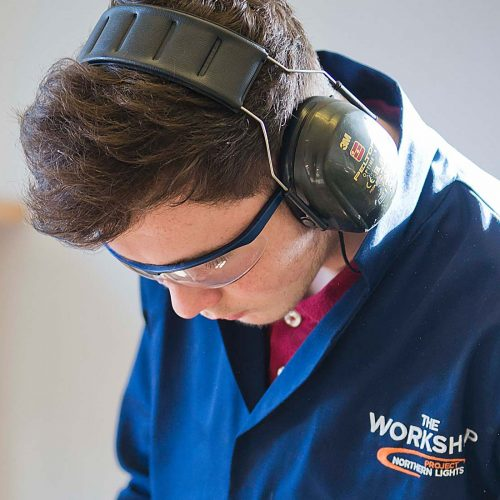 An image of a young male with protective eye glasses and earphones working for the Aberfeldy Community Workshop a charity supported by the Ellis Campbell Foundation, helping disadvantaged young people in Hampshire, London and Perthshire