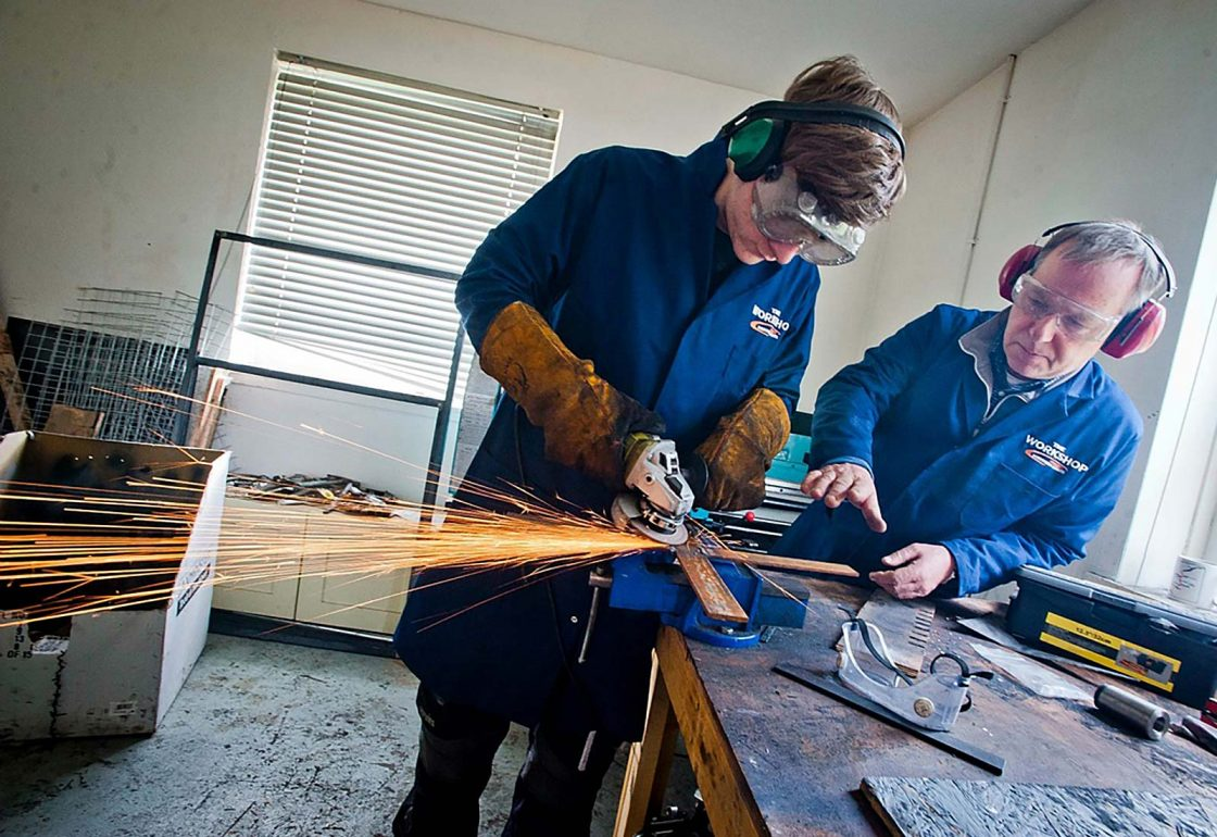 An image of a young male with teacher both with protective eye glasses and earphones working for the Aberfeldy Community Workshop a charity supported by the Ellis Campbell Foundation, helping disadvantaged young people in Hampshire, London and Perthshire