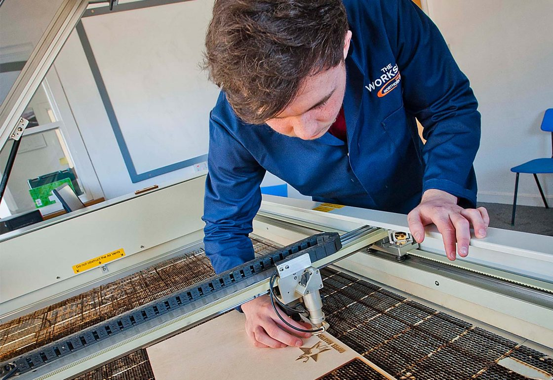 An image of a young male using a laser cutter working for the Aberfeldy Community Workshop a charity supported by the Ellis Campbell Foundation, helping disadvantaged young people in Hampshire, London and Perthshire