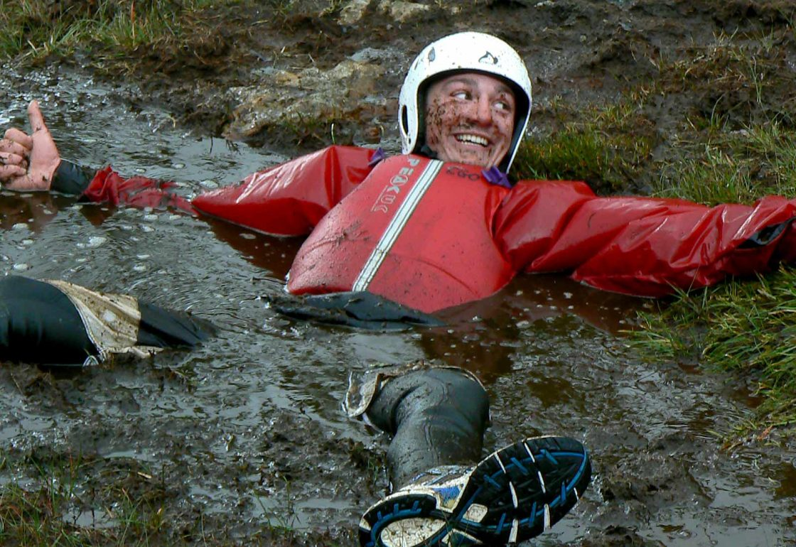 An image of a guy lying in mud and water taking part a Climbing Out activity , a charity supported by the Ellis Campbell Foundation, helping disadvantaged young people in Hampshire, London and Perthshire