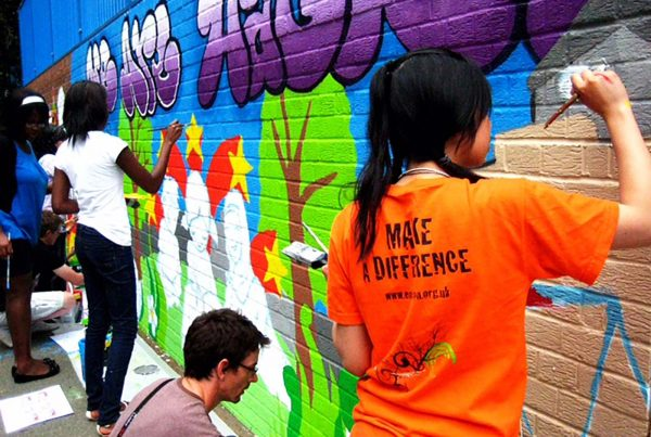 An image of young people painting a graffiti mural on a wall, representing the Envision Community Apprenticeship Programme, a charity supported by the Ellis Campbell Foundation, helping disadvantaged young people in Hampshire, London and Perthshire
