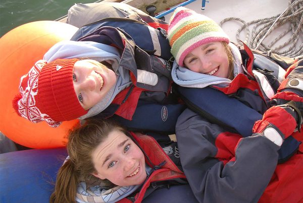 An image of three young people smiling aboard a sailing boat part of Ocean Youth Trust South, a charity supported by the Ellis Campbell Foundation, helping disadvantaged young people in Hampshire, London and Perthshire