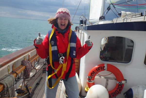 An image of a smiling female teenager enjoying sailing aboard the Prolific sailing boat part of Ocean Youth Trust South, a charity supported by the Ellis Campbell Foundation, helping disadvantaged young people in Hampshire, London and Perthshire