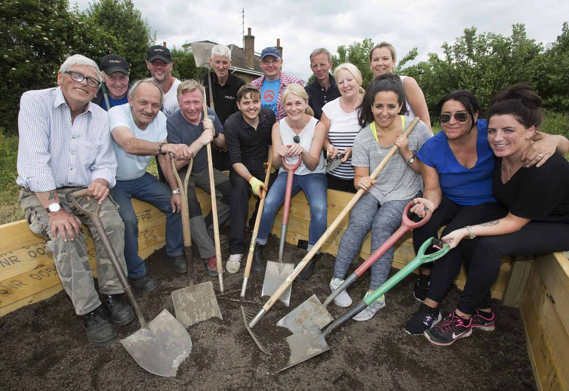 An image of a group of people of mixed ages with spades in hand helping with a gardening project representing Young Enterprise Scotland a grant by the Ellis Campbell Foundation helping disadvantaged young people in Hampshire, London and Perthshire