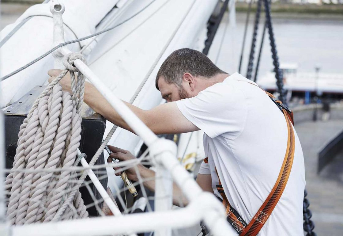 An image of a man fixing the rigging on the Cutty Sark representing the Lifeboats Conservation Project grant at the Royal Museum Greenwich made by the Ellis Campbell Foundation helping disadvantaged young people in Hampshire, London and Perthshire