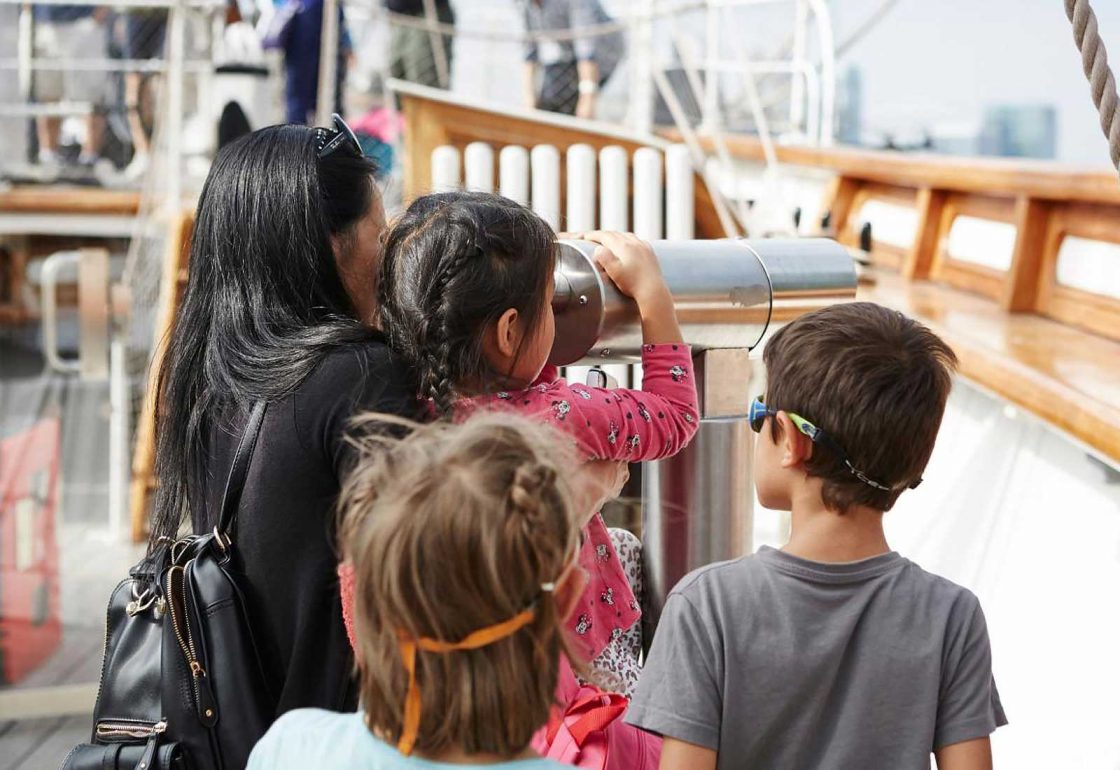 An image of children aboard the Cutty Sark looking through a telescope representing the Lifeboats Conservation Project grant at the Royal Museum Greenwich made by the Ellis Campbell Foundation helping disadvantaged young people in Hampshire, London and Perthshire