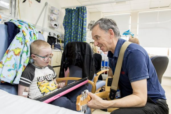 A colour image of a man playing a guitar to a sick child in hospital - part of Young Sparks supported by the Kensington & Chelsea Foundation - A grant made by The Ellis Campbell Foundation