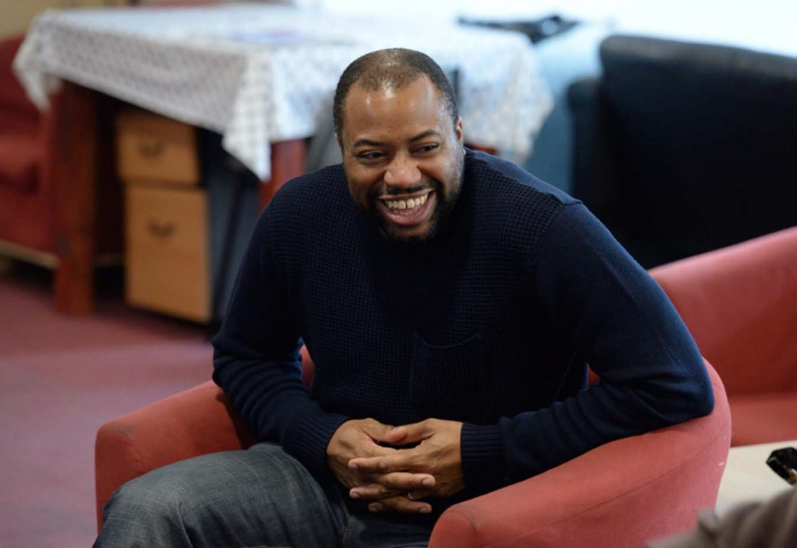 A colour image of a smiling black man in trousers and navy jumper taking part in the Khulisa Face It arts programme supported by the Ellis Campbell Foundation