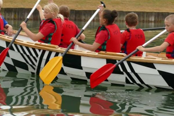 A colour image of a young people sat in a rowing boat on water, wearing red life jackets taking part in the Oarsome Chance programme supported by the Ellis Campbell Foundation