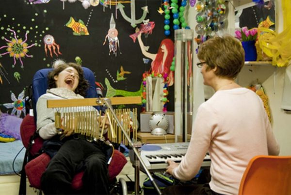 A colour image of young smiling disabled girl playing musical instruments part of Parity for disability supported by the Ellis Campbell Foundation
