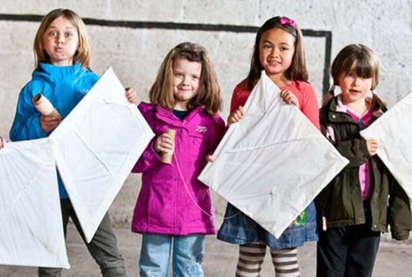 A colour image of six young girls standing in a line holding kites they have made as part of the Remake Scotland Craft Initiative supported by the Ellis Campbell Foundation