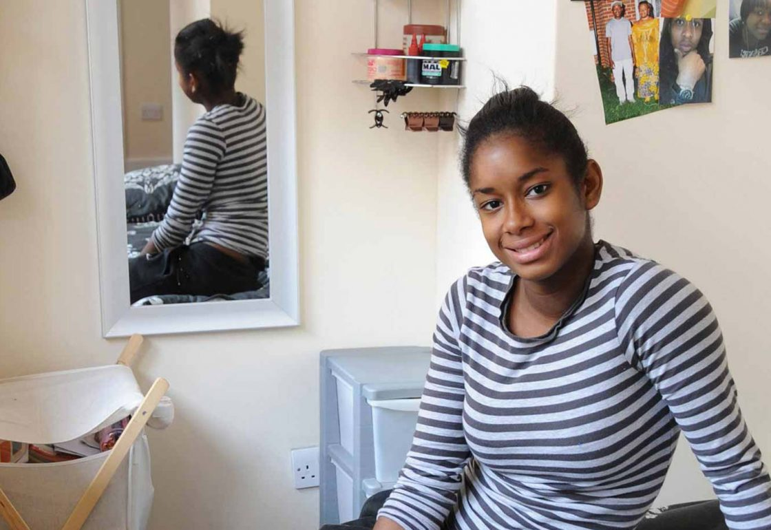 A colour image of a young black smiling female sat in her bedroom, part of the Centrepoint programme to help the homeless supported by The Ellis Campbell Foundation