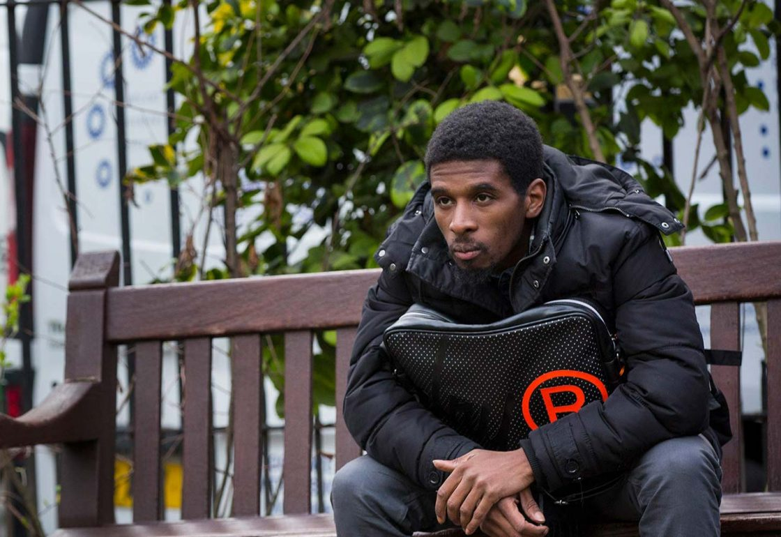 An image if a young black male sat on a wooden bench helped by Centrepoint - Helping the Homeless supported by The Ellis Campbell Foundation