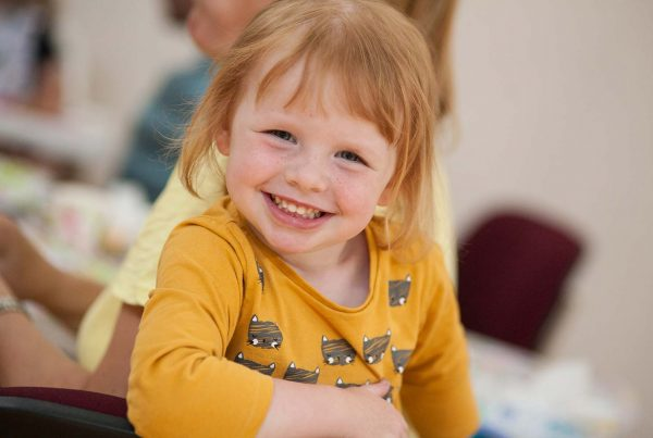 An image of a little girl with red hair smiling - supported by KIDS - The Ellis Campbell Foundation