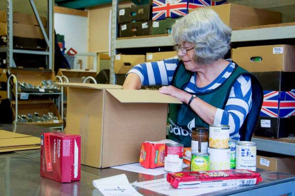 Lady volunteer packing a food box at the Trussell Trust supported by the Ellis Campbell Foundation